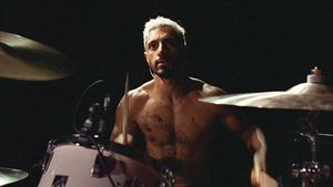 Riz Ahmed at a drum kit